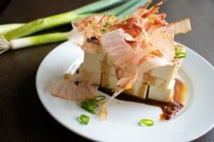 japanese tofu salad with bonito flakes on white round plate