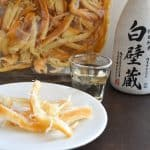 Japanese dried squid on plate with bottle of junmai sake