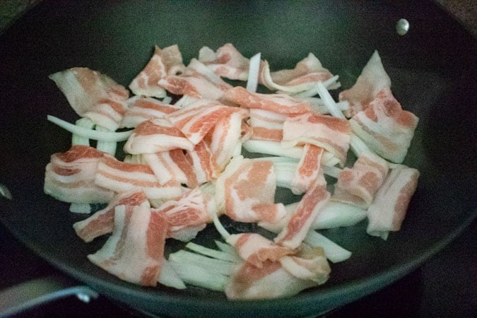 sliced pork belly and onion in wok