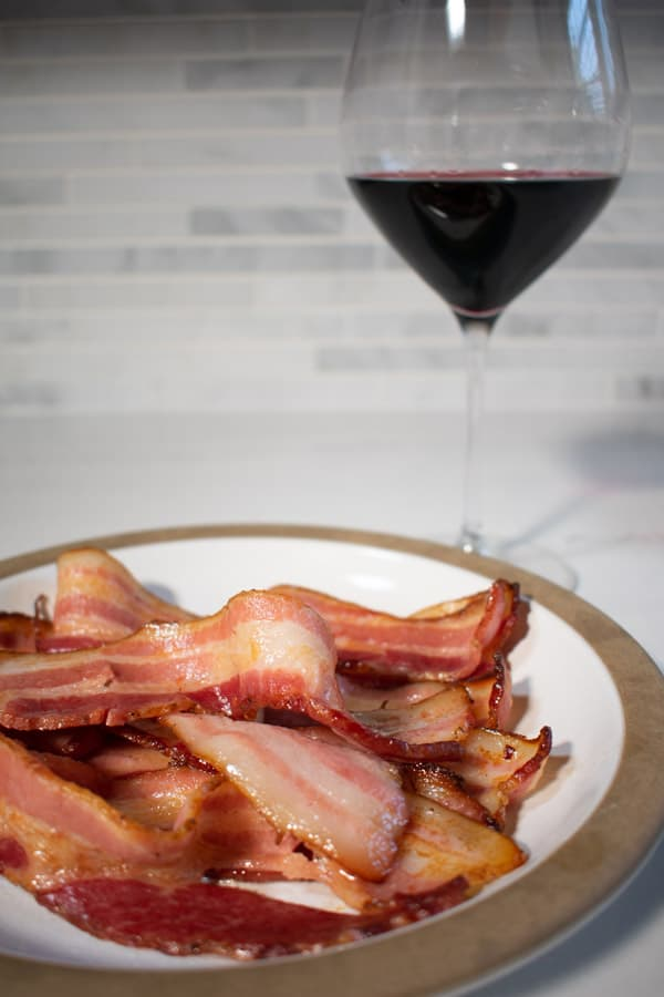 bacon strips on plate with glass of red wine