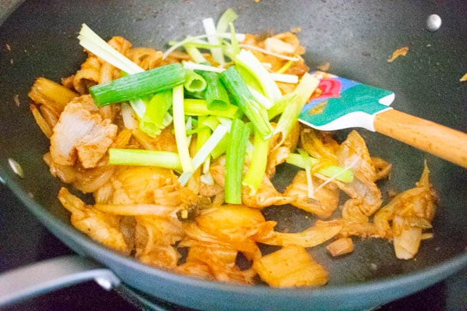 kimchi pork belly with green onion in wok