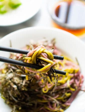 purple and green soba noodles on chopsticks
