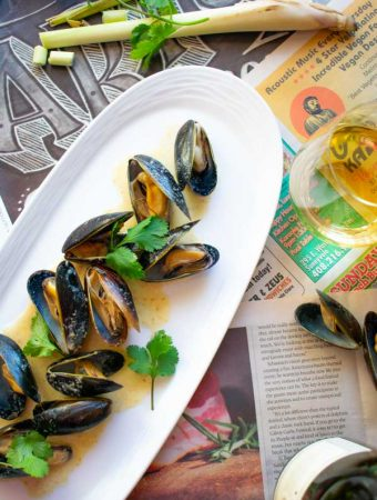 Easy Thai Coconut Curry Mussels on white plate with white wine glass