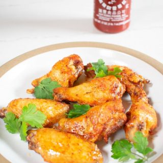 sriracha buffalo wings on plate with sriracha bottle