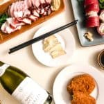 bottle of chablis wine with sushi plates, brie cheese, and potato croquettes