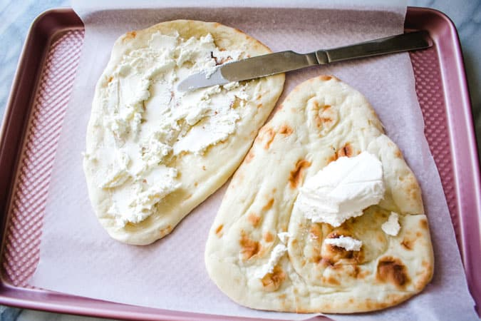 fromage blance spread onto naan on pink sheet pan for asian alsatian pizza