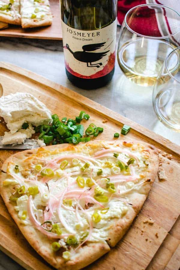 asian alsatian pizza on wood cutting board with glasses of auxerrois wine