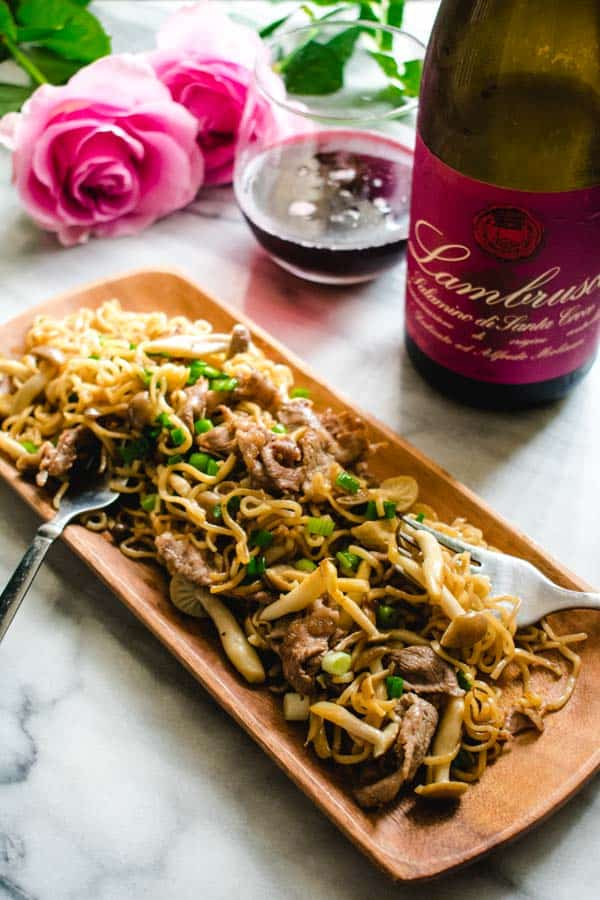 beef ramen noodle stir fry on wood plate with lambrusco wine