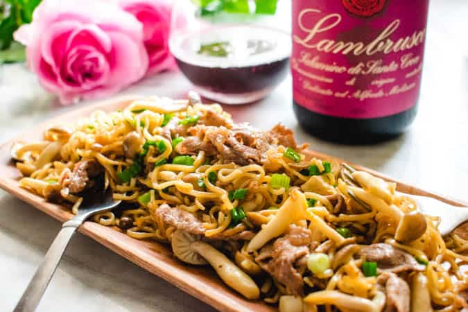 Ramen noodle stir fry with beef and mushrooms on a wooden rectangular plate. Red wine and pink roses in the background.