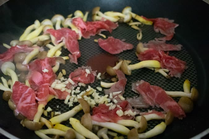 Thin slices beef cooking in a nonstick pan with bunapi mushrooms