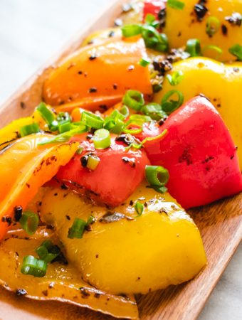 Mixed colored bell peppers with green onion on long wooden plate