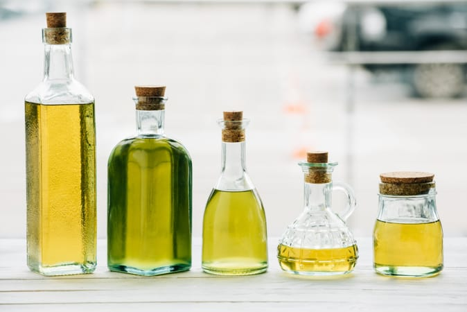 5 clear glass bottles of cooking oil in various heights and shapes, all with wooden corks.