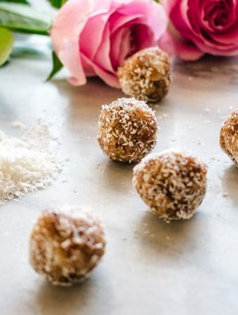 7 Coconut Date balls on marble board with 2 pink roses in the background.