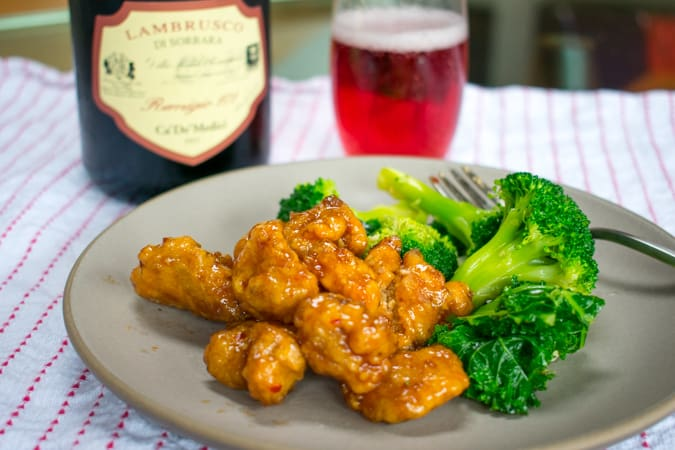 Orange chicken and broccoli with glass and bottle of Lambrusco sorbara wine