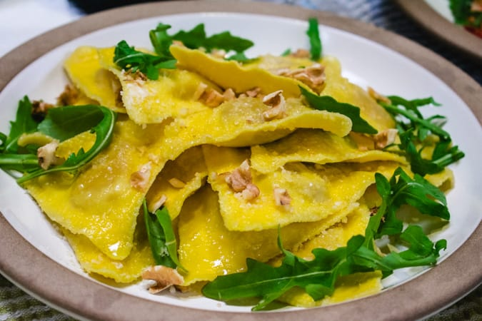 Trader Joe's butternut squash ravioli with arugula leaves and walnuts