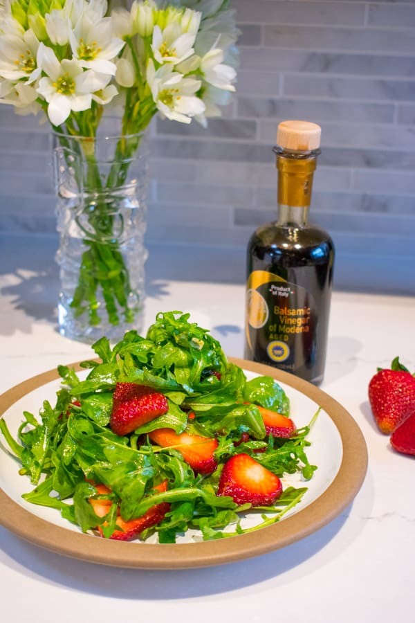 strawberry arugula salad with bottle of balsamic vinegar of modena and vase of white flowers
