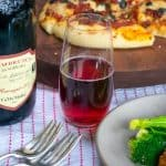 Bottle and glass of Lambrusco sorbara wine with pizza in the background