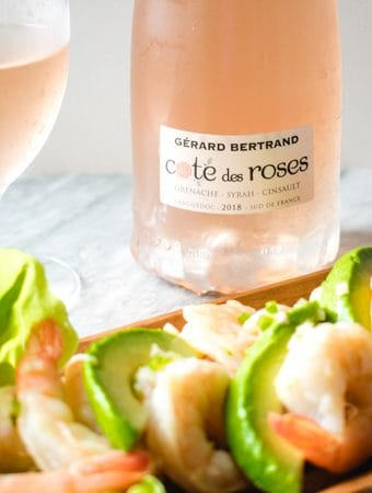 Shrimp and avocado salad in front of a bottle and glass of Gerard Bertrand rose