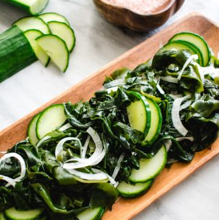 Korean seaweed salad on rectangular wooden plate with chopped cucumber and wooden bowl of pink salt in the background.