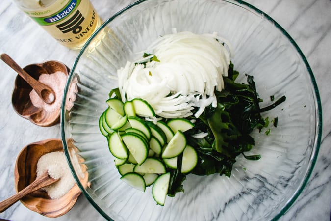 Chopped seaweed, white onion, and english cucumber in glass bowl.