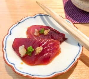 Two slices of bonito tuna on a white plate with chopsticks on the side.