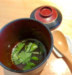 Red bowl of seaweed soup with wooden spoon on the side.