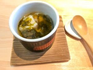 Cup of egg custard set on a brown square napkin with wooden spoon on the side.