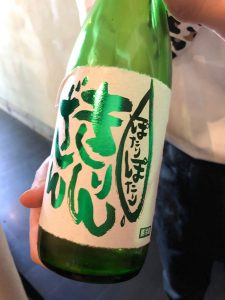 green bottle of sake with white later and Japanese characters in green.