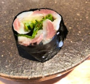 Slice of sardine wrapped in nori on a round granite plate.