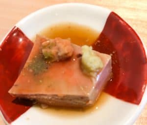 Square of monkfish liver on a small red and white plate