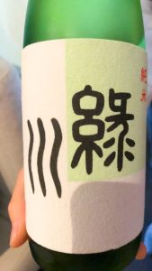 Green bottle of sake with a white label