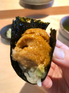 Hand holding a seaweed handroll with uni