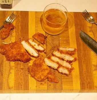 Sliced Japanese pork cutlet on a wooden cutting board with a glass of beer.