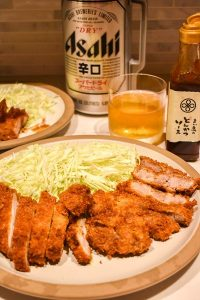 Pork tonkatsu and shredded cabbage on a plate with Asahi beer in the background.