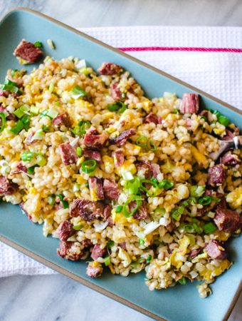 corned beef fried rice on rectangle blue plate on a white towel