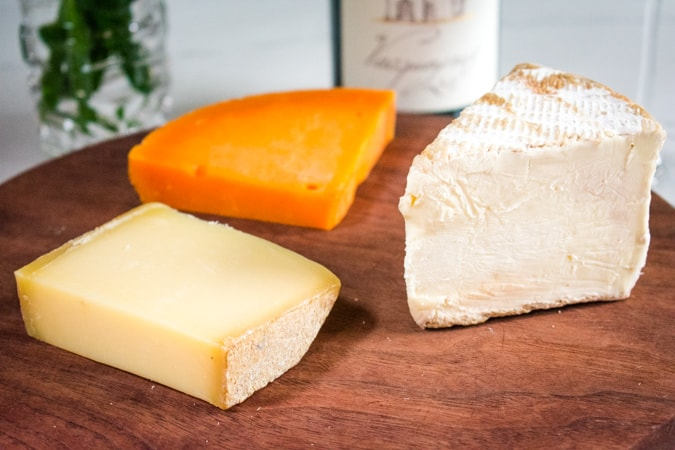 Comte, Mimolette, and Saint Andre Triple Creme Brie Cheeses on a brown round cutting board