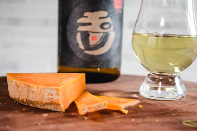 French Mimolette Cheese with a glass and bottle of Genshu Sake
