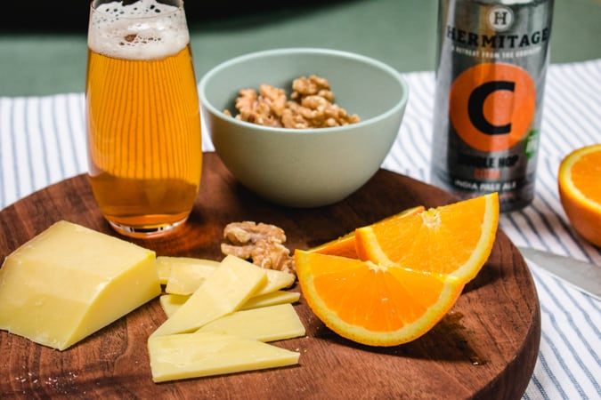 Comte cheese on a round wood cutting board with a IPA beer, walnuts, and orange slices.