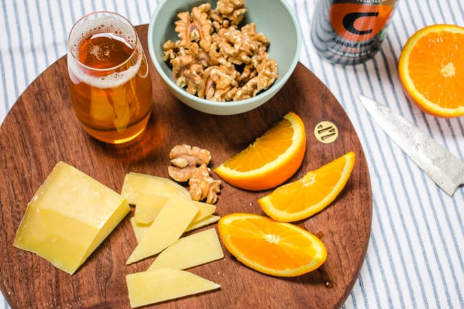 Comte cheese, orange slices, walnuts, and IPA beer on a round wooden cutting board.