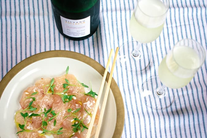 Plate of yellowtail crudo with chopsticks and 2 glasses and bottle of prosecco wine on a blue and white striped tablecloth.