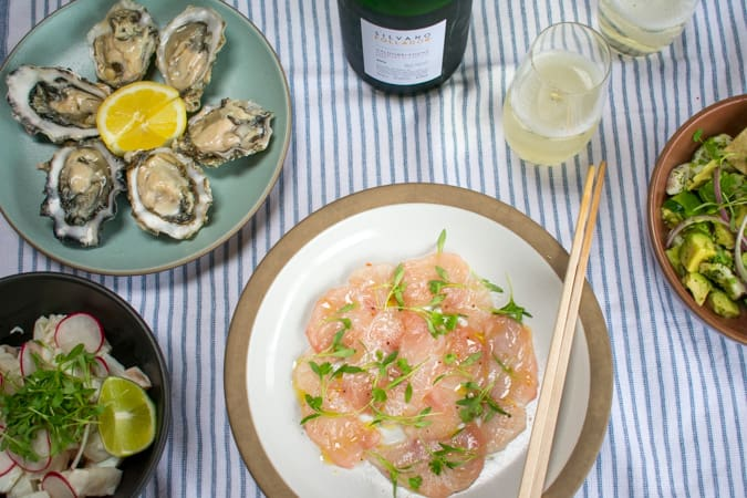 Plate of oysters and plate of hamachi carpaccio with prosecco wine.