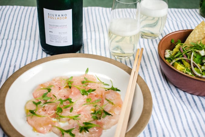 2 glasses and bottle of cartizze prosecco, plate of hamachi carpaccio with chopsticks, and bowl of aguachile ceviche