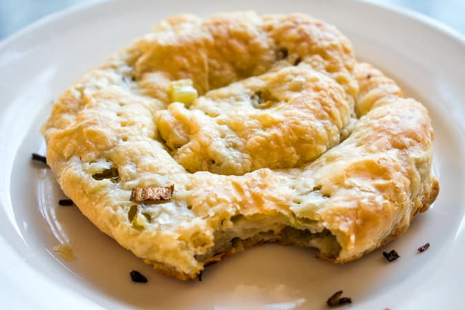 Puff pastry scallion pancake with a bite taken out of it on a white round plate