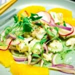 Aguachile ceviche with orange slices on a blue plae