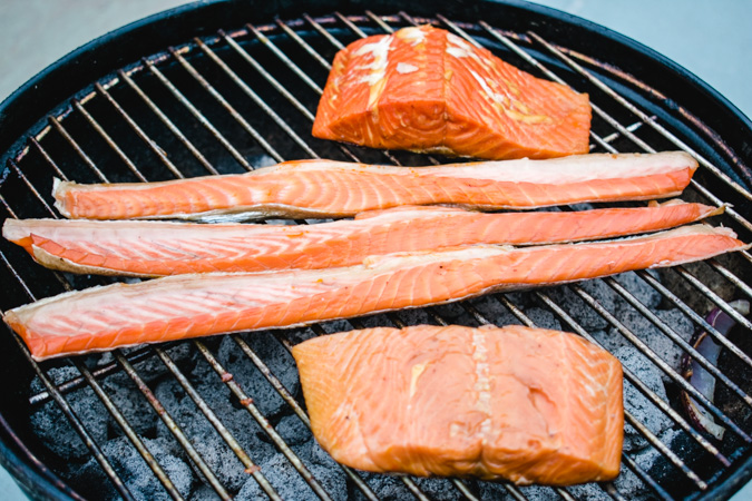 Fillets of smoked sockeye, coho bellies, and coho salmon on a charcoal grill