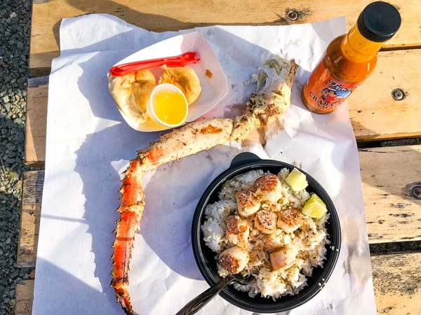 King Crab Leg, Scallops over rice, bread roll and butter, and Tracy's crabcake sauce on a picnic table