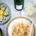 Plates of oysters, hamachi carpaccio, and ceviche with 2 glasses of cartizze prosecco