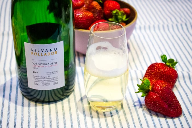 "2016 Silvano Follador ""Cartizze"" Prosecco Superiore Brut Nature with a bowl of strawberries on a blue and white striped tablecloth."