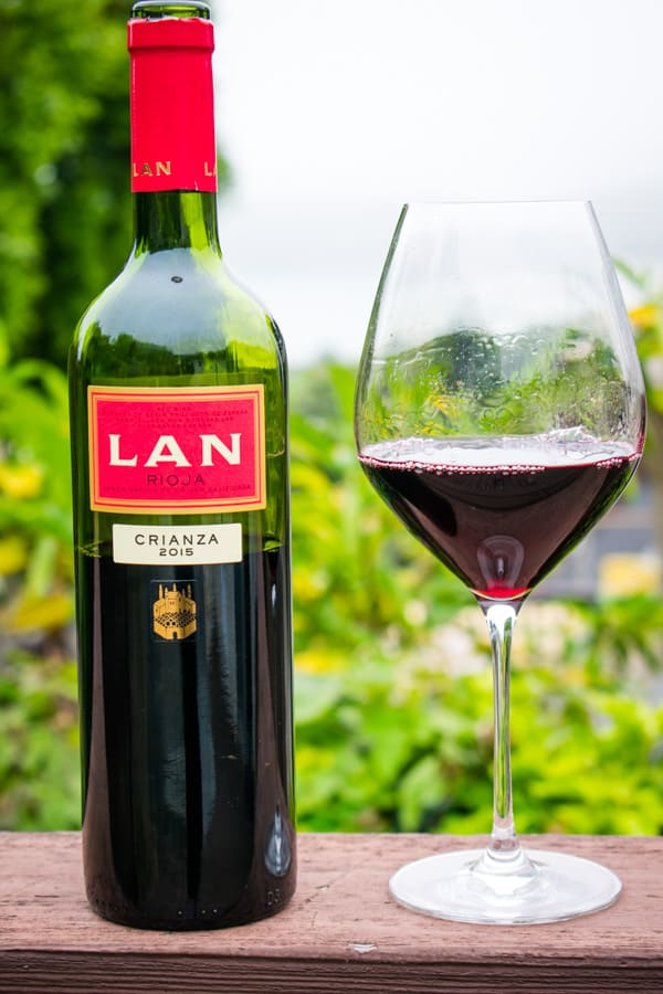 Bottle and wine glass of 2015 Bodega LAN Crianza Rioja with green plants in the background
