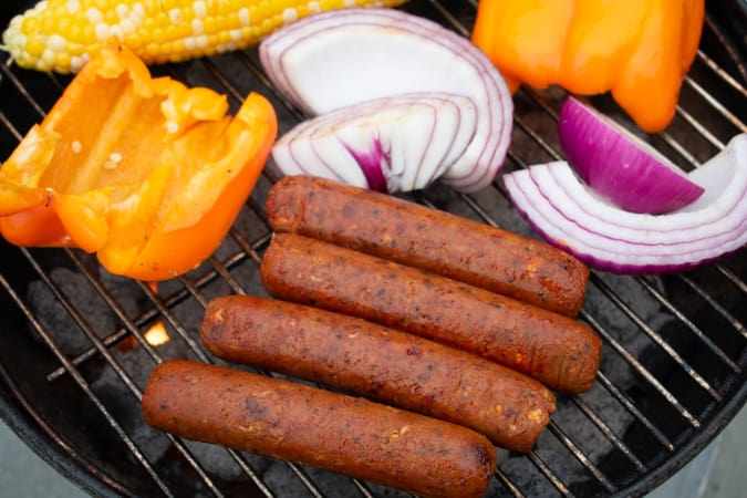 Vegan Field Roast Mexican Chorizo Sausages on the grill with red onion and yellow bell pepper